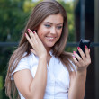 Stock Photo: Young womlooks in phone and rejoices
