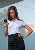 Young woman with a mobile phone in hands — Stock Photo