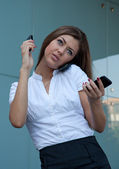 Young woman talks by three phones simultaneously — Stock Photo