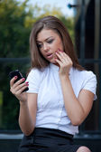 Young woman looks in phone and is surprised — Stock Photo
