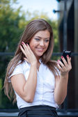 Young woman looks in phone and rejoices — Stock Photo
