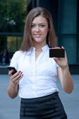 Young woman with phone and credit card in hands — Stock Photo