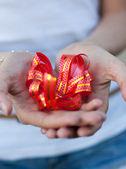 Giovane donna tiene un fiocco regalo nelle mani — Foto Stock
