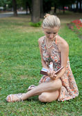 Young woman reads the book sits on a green grass — Stock Photo
