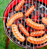 Fried sausages on a grill — Stock Photo