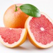 Grapefruits and segments with a leaf on a white background - Stock Photo