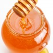 Royalty-Free Stock Photo: Full honey pot and spilled honey on a white background.