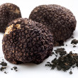 Black truffles with the pieces of soil on a white background - Stock Photo