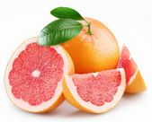 Grapefruits and segments with a leaves on a white background — Stock Photo