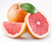 Grapefruits and segments with a leaf on a white background — Stock Photo