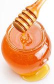 Full honey pot and spilled honey on a white background. — Stock Photo