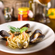 Italian spagetti with mussels and basil on a wooden table - Stock Photo