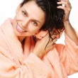 Smiling young woman drying hair with towel in a bathrobe on a white backgr — Stockfoto