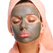 Close face of young woman with a mud mask on it. Isolated on a white backgr — Stock Photo #3611362