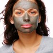 A funny girl with  mud mask on a white backgroung - Stock Photo