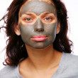 Royalty-Free Stock Photo: A funny girl with  mud mask on a white backgroung