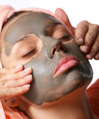 Beauty-spa. Applying of cosmetic mud mask. Close face of young woman — Stockfoto