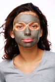 A funny girl with mud mask on a white backgroung — Stock Photo