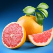Ripe grapefruit with section on a blue background — Photo