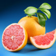 Ripe grapefruit with section on a blue background — Stockfoto