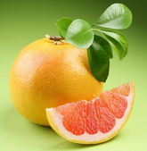 Ripe grapefruit with segment on a green background — Stock Photo