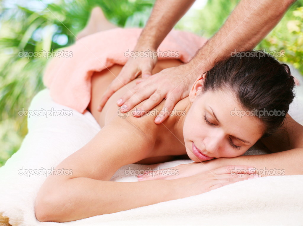 Young woman gets a massage. Eyes are closed.  Foto de Stock   #3658371