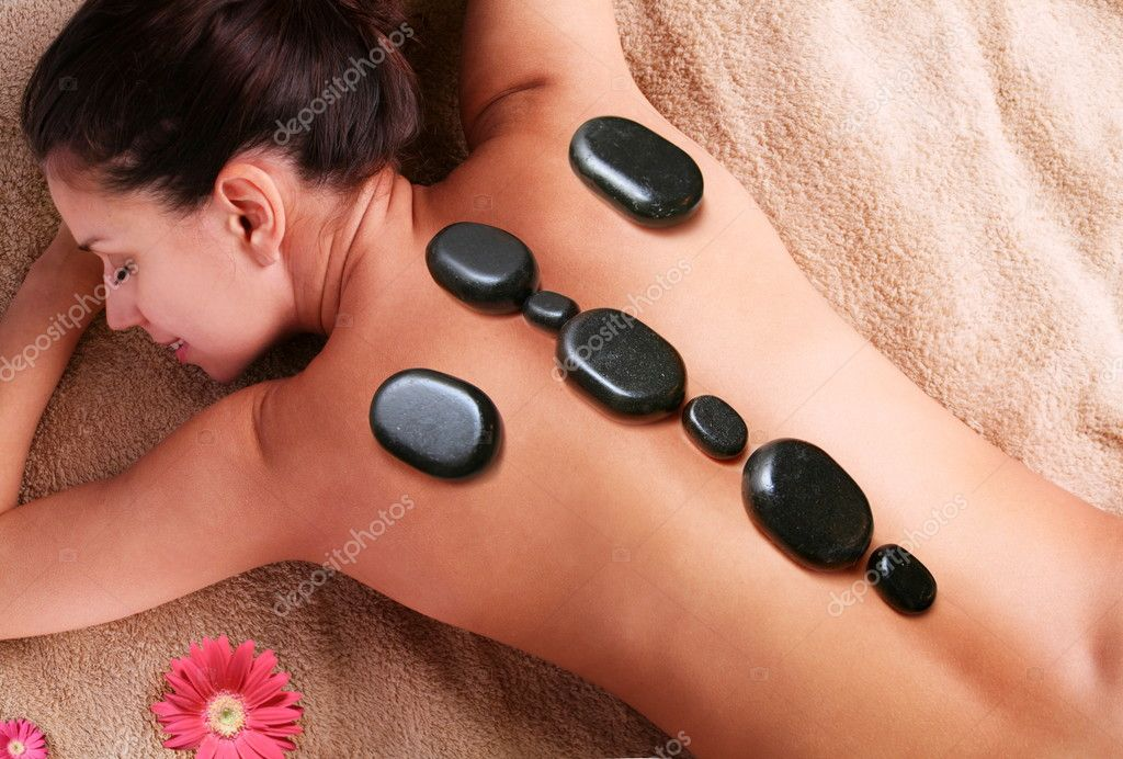 Smiling young woman getting pleasure of stone therapy. Eyes are closed. — Stock Photo #3658390
