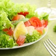 Fresh salad with tomatoes and salmon in a white bowl on a green tablecloth — Stock Photo