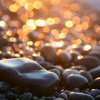 Background with sea stones and orange blurred circles. — Stock Photo