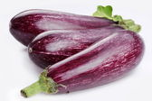 Purple eggplants with leaves on white background — Stock Photo