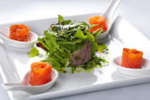 Salmon in a white plate. In the middle of rucola salad. — Stock Photo