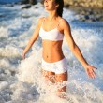 Happy beautiful girl in the sea waves — Stock Photo