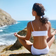 Stock Photo: Woman meditating on a rocky seashore