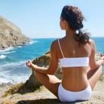 Woman meditating on a rocky seashore — Stock Photo #3853491