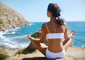 Woman meditating on a rocky seashore — Stock Photo