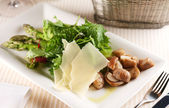 Salad with porcini mushrooms and arugula on a white plate — Stock Photo