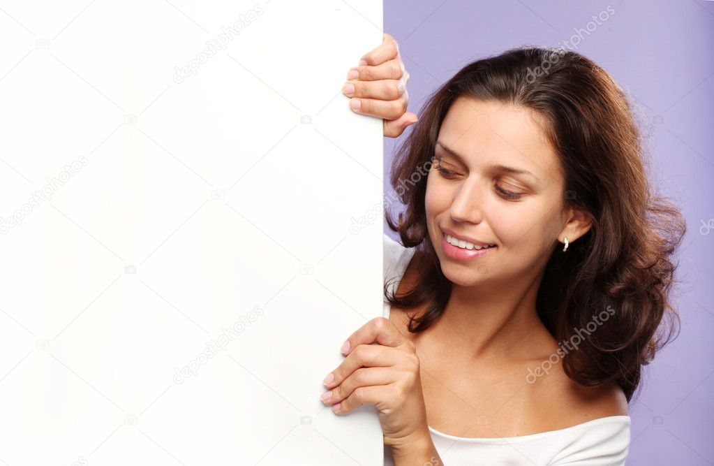 Beautiful brunette holding the edge of a white billboard  Stock Photo #3854038