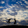 Figures of jumping on a hill on a background a cloud and the coming — Stock Photo