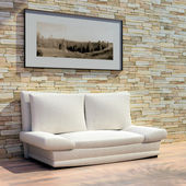 3d rendering. Cosy light sofa from a fabric near a stone wall with a pictur — Stockfoto