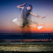Extreme dance on the brink of a roof against a decline — Stock Photo
