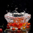 Sweet cherries in glass to a basket with water and sparks on a mirror — Stock Photo