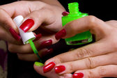 The master does manicure to the girl of bright green color — Stock Photo