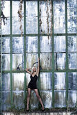 Beautiful woman stands near glass wall — Stock Photo
