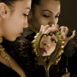 Reflection of the girl in mirrors with an antiquarian frame from gold — Stock Photo