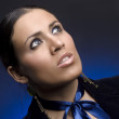 Stylish young lady with a dark blue bow on a dark blue background — Stock Photo