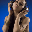 The girl with headphones on a dark blue background — Stock Photo