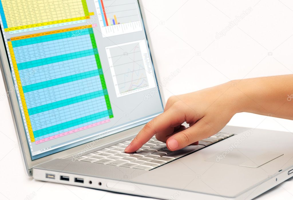 Image shows a finger pressing a key on a contemporary laptop  displaying a business spreadsheet — Stock Photo #3393553