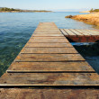 Wooden pier in Greece extending into the sea - Stock Photo