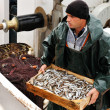 Fisherman carrying box with fish - Stock Photo