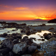 Glorious sunset over rocky sea - Stock Photo